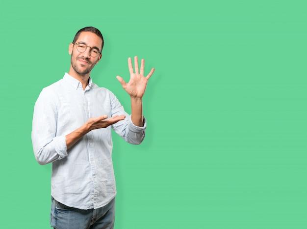Młody człowiek robi gestowi numerowi pięć