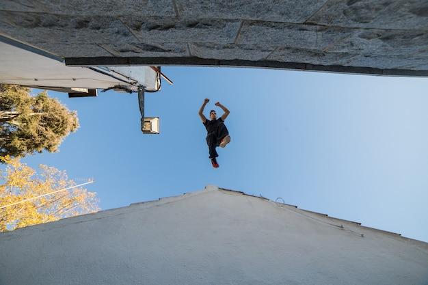 Młody człowiek robi imponujący skok parkour z jednego dachu na drugi