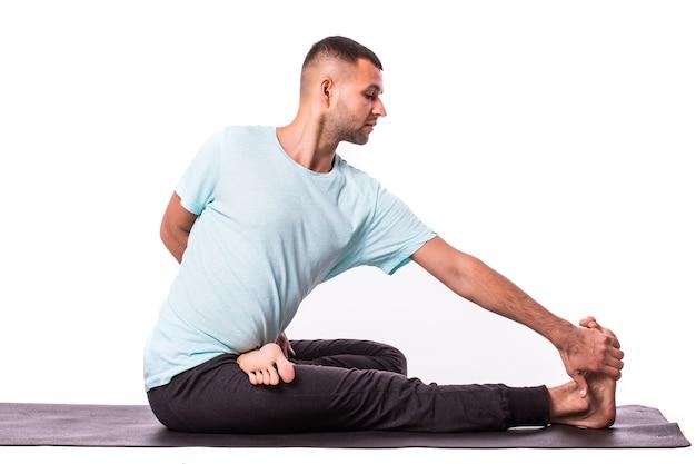 Młody człowiek robi joga na białym tle nad białym tle