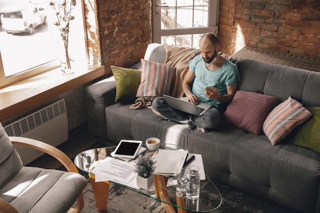 Młody człowiek robi jogę w domu podczas kwarantanny i pracy jako freelancer