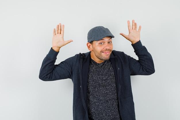 Młody człowiek robi kapitulacji gest i uśmiecha się w t-shirt, kurtka, widok z przodu czapki.