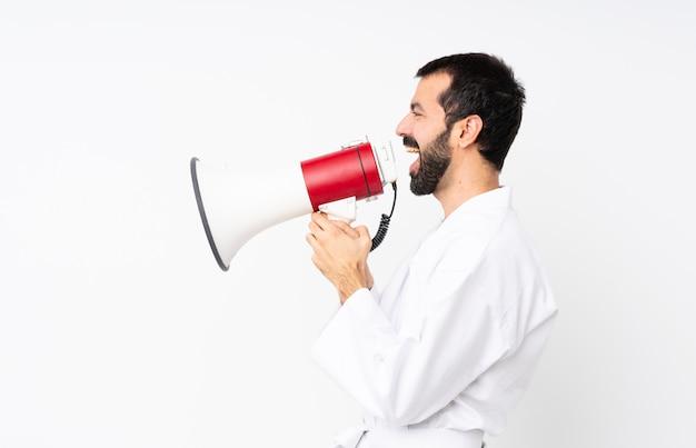 Młody człowiek robi karate krzyczy przez megafon