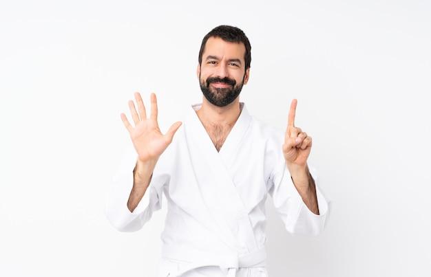 Młody człowiek robi karate na białym licząc sześć palcami