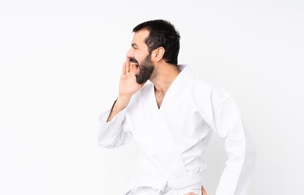Młody człowiek robi karate na białym tle krzyczy z szeroko otwartymi ustami do boku