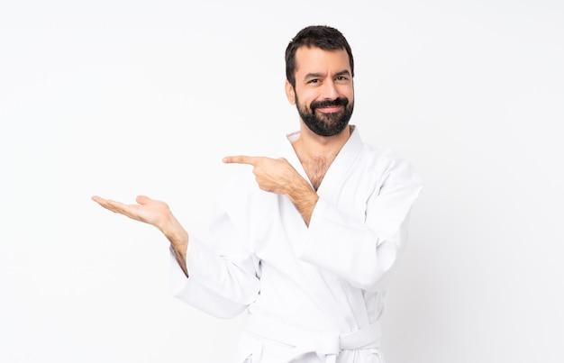 Młody człowiek robi karate nad białym gospodarstwa wyobraźni copyspace na dłoni, aby wstawić reklamę