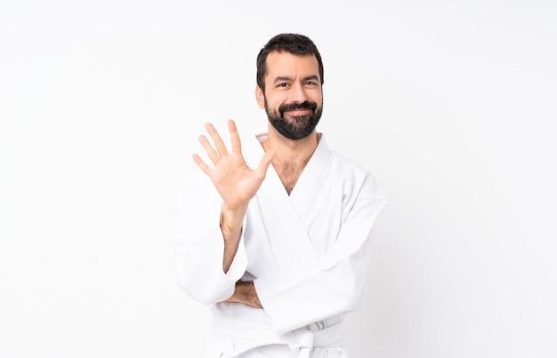 Młody człowiek robi karate nad odosobnioną biel ścianą liczy pięć z palcami