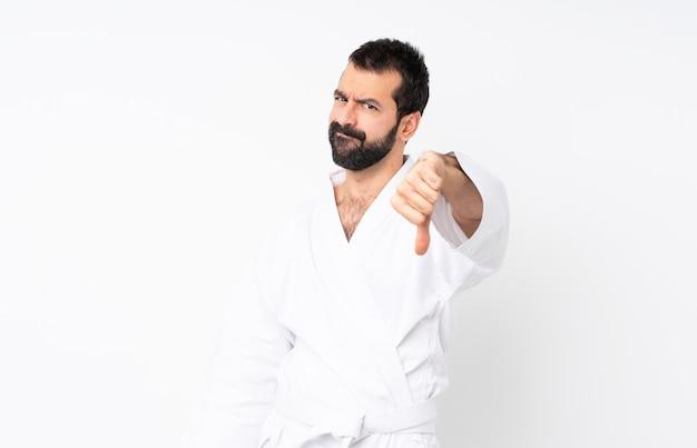 Młody człowiek robi karate nad odosobnioną biel ścianą pokazuje kciuka puszek z negatywnym wyrażeniem
