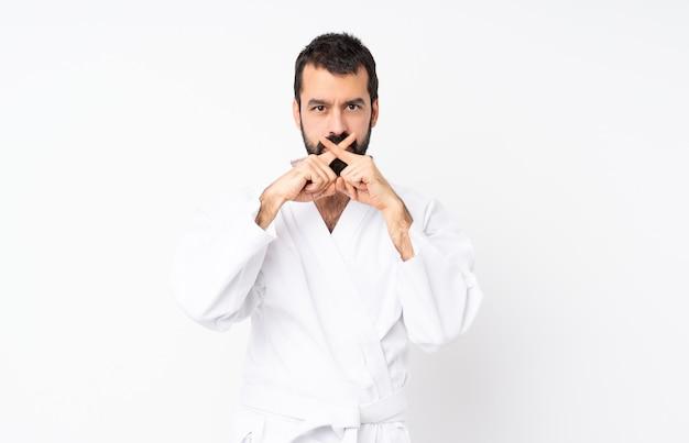 Młody człowiek robi karate nad odosobnionym bielem pokazuje znaka cisza gest