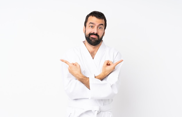 Młody człowiek robi karate nad odosobnionym bielem wskazuje laterals ma wątpliwości