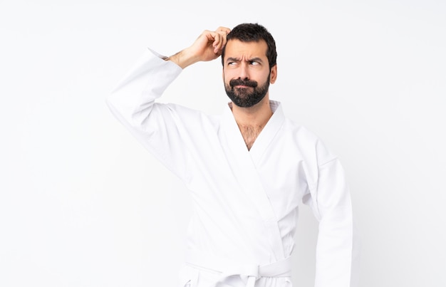 Młody człowiek robi karate nad odosobnionym mieć wątpliwości podczas gdy drapający głowę