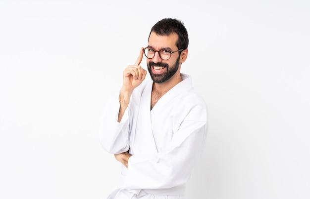 Młody człowiek robi karate nad odosobnionym z szkłami i ono uśmiecha się
