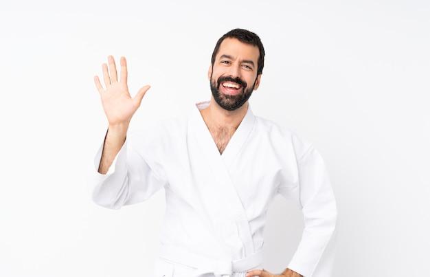 Młody człowiek robi karate pozdrawiając ręką z happy wypowiedzi
