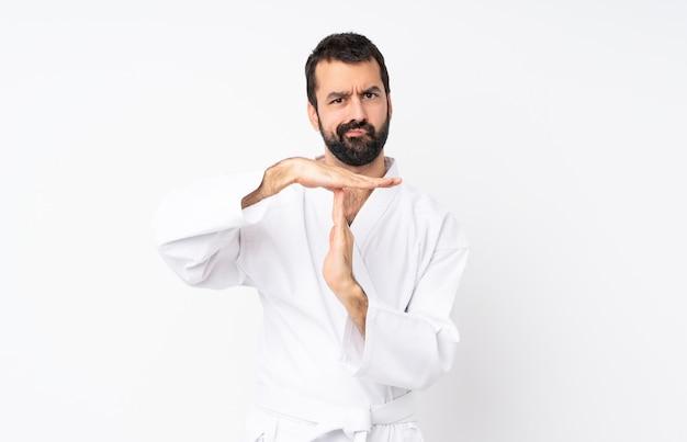 Młody człowiek robi karate robi czasowi out gestykuluje