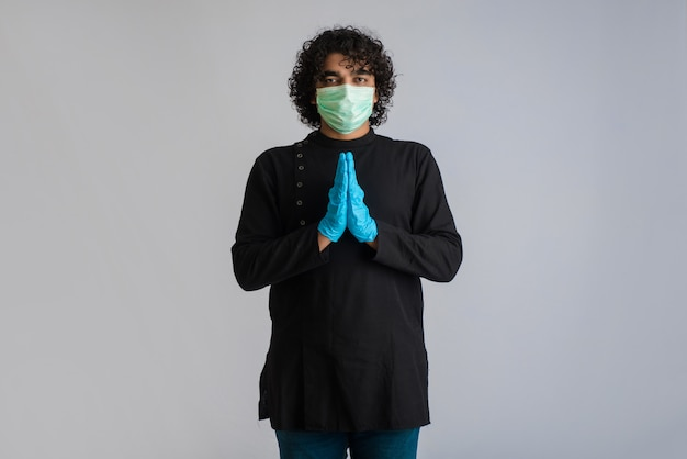 Młody człowiek robi namaste z powodu wybuchu covid-19. nowe powitanie, aby uniknąć rozprzestrzeniania się koronawirusa zamiast powitania uściskiem lub uściskiem dłoni. praktyka jogi dla równowagi psychicznej.