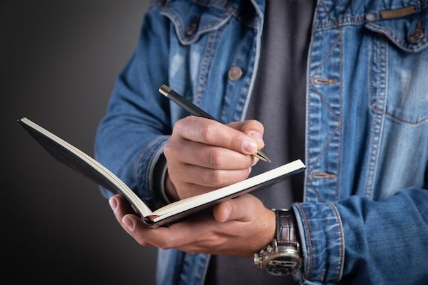 Młody człowiek robi notatki w zeszycie