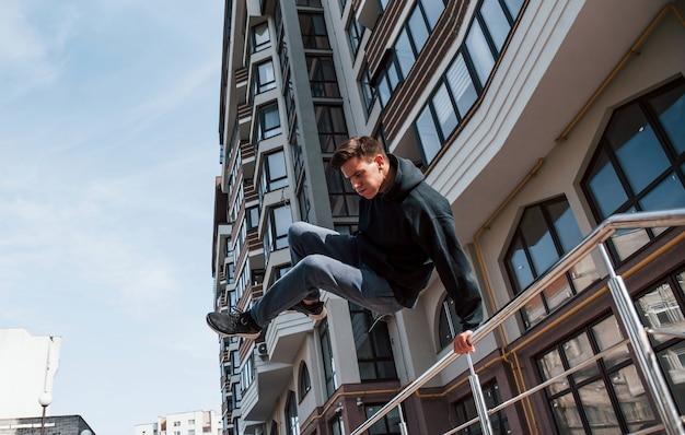 Młody człowiek robi parkour w mieście w ciągu dnia. koncepcja sportów ekstremalnych.