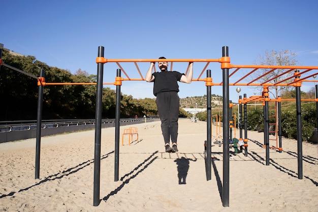 Młody człowiek robi podciągnięcie, kalistenika. ćwiczenia ze sztangą na świeżym powietrzu, fitness, sport, trening i koncepcja stylu życia.