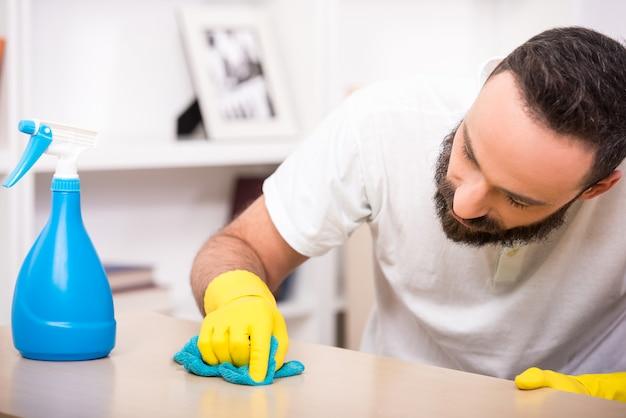 Młody człowiek robi prace porządkowe w domu.