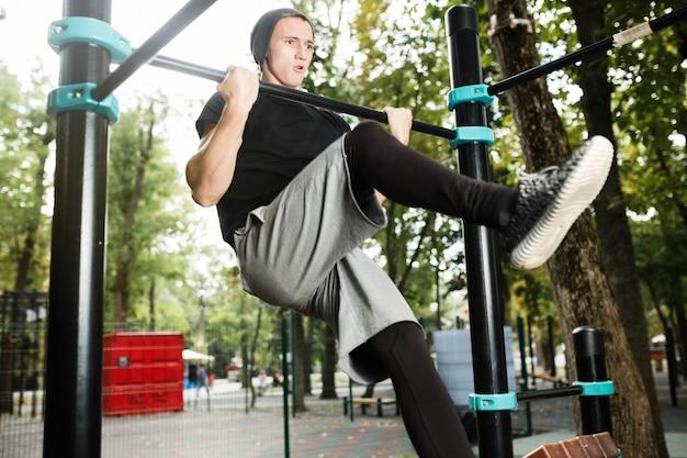 Młody człowiek robi pull up na drążku na zewnątrz, trening, koncepcja sportu.
