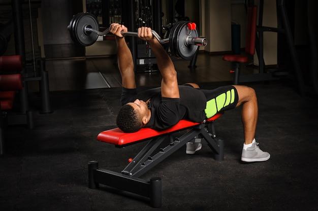 Młody człowiek robi ręce ławki francuskiej prasy treningu w siłowni