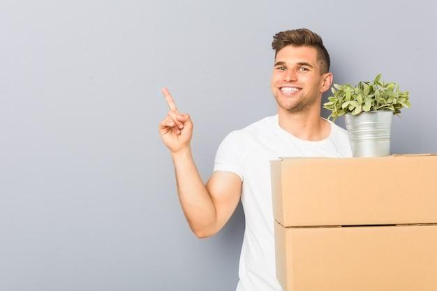 Młody człowiek robi ruch gospodarstwa pudełka uśmiecha się wesoło wskazując palcem wskazującym daleko.