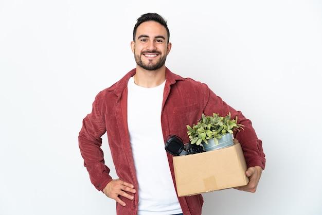 Młody człowiek robi ruch, podnosząc pudełko pełne rzeczy na białej ścianie, pozuje z rękami na biodrze i uśmiecha się