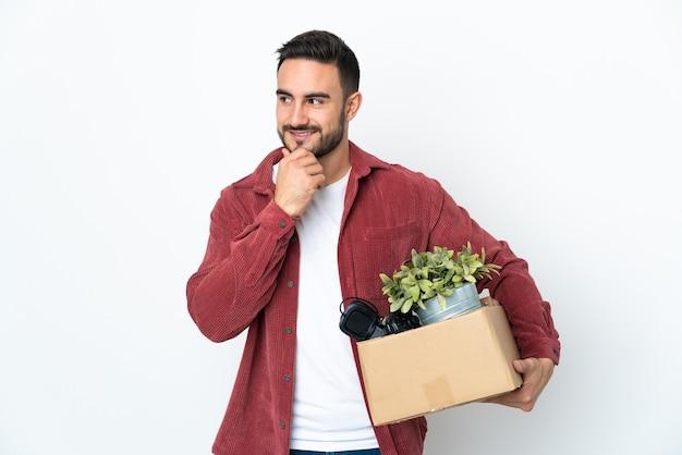 Młody człowiek robi ruch, podnosząc pudełko pełne rzeczy na białym tle na białej ścianie, patrząc z boku i uśmiechając się