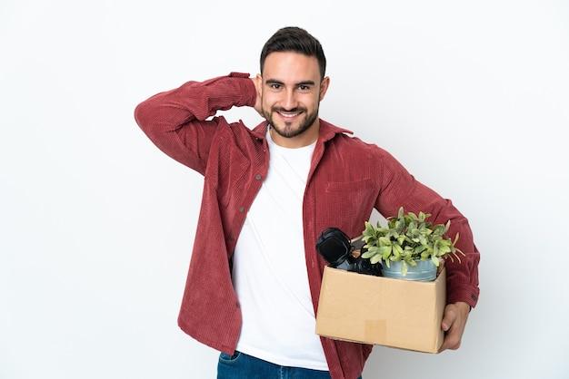 Młody człowiek robi ruch podnosząc pudełko pełne rzeczy na białym tle na białej ścianie, śmiejąc się