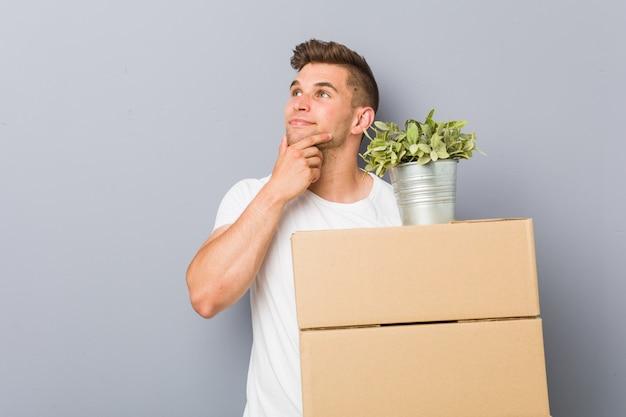 Młody człowiek robi ruch trzyma pudełka patrzeje z ukosa z wątpliwym i sceptycznym wyrażeniem.