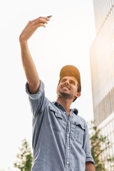 Młody człowiek robi selfie poza