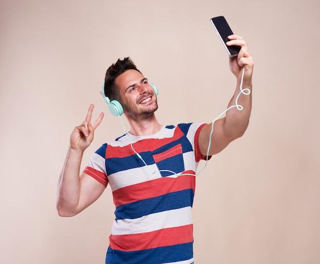 Młody człowiek robi selfie w studio strzał