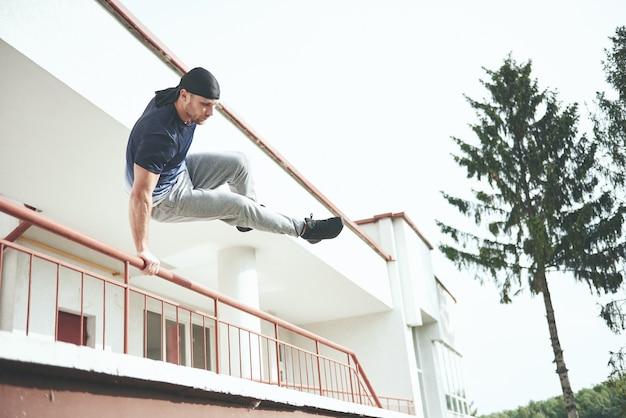 Młody człowiek robi skok parkour w przestrzeni miejskiej w słoneczny wiosenny letni dzień miasta.