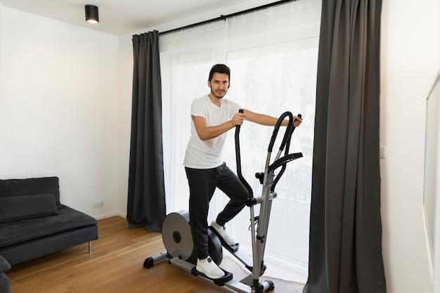 Młody człowiek robi sportom w domu