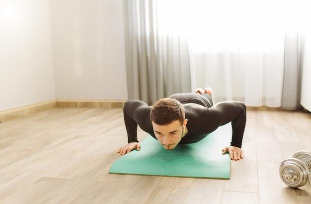 Młody człowiek robi sportowi ćwiczy w domu