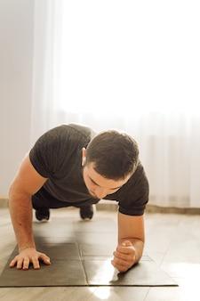 Młody człowiek robi sprawności fizycznej ćwiczeniu w domu