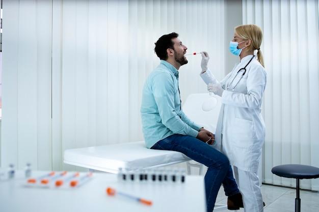 Młody człowiek robi test pcr w gabinecie lekarskim podczas epidemii wirusa koronowego