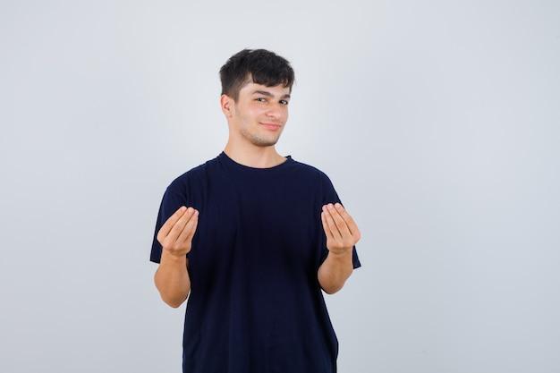 Młody człowiek robi włoski gest w czarną koszulkę i patrząc pewnie, z przodu.
