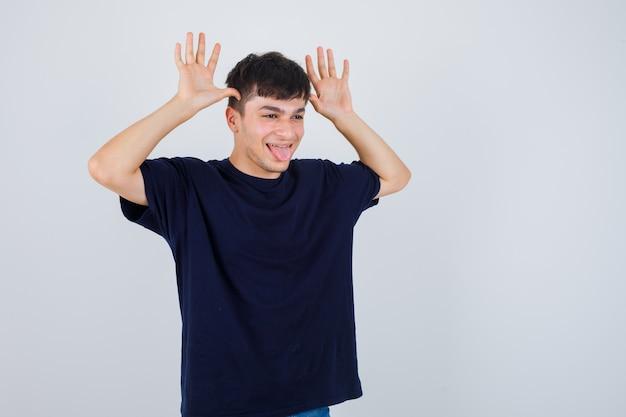 Młody człowiek robi zabawny gest, wystający język w czarnej koszulce i patrząc rozbawiony, widok z przodu.