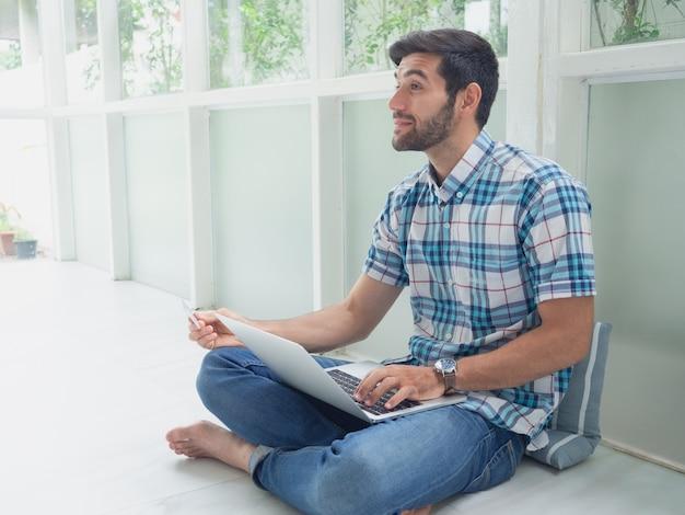 Młody człowiek robi zakupy online z kartą kredytową w domu
