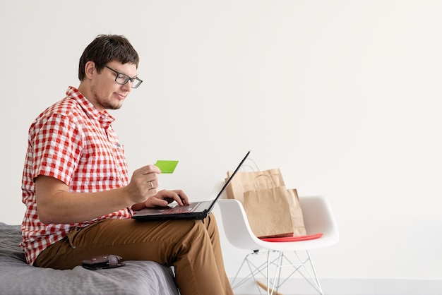 Młody człowiek robi zakupy w internecie z laptopem