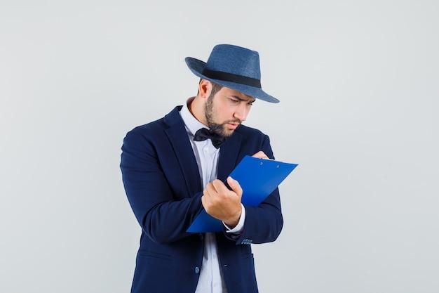 Młody człowiek robienie notatek w schowku w garniturze, kapeluszu i patrząc zajęty. przedni widok.