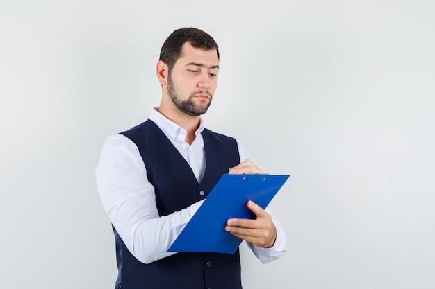 Młody człowiek robienie notatek w schowku w koszuli i kamizelce i patrząc zajęty
