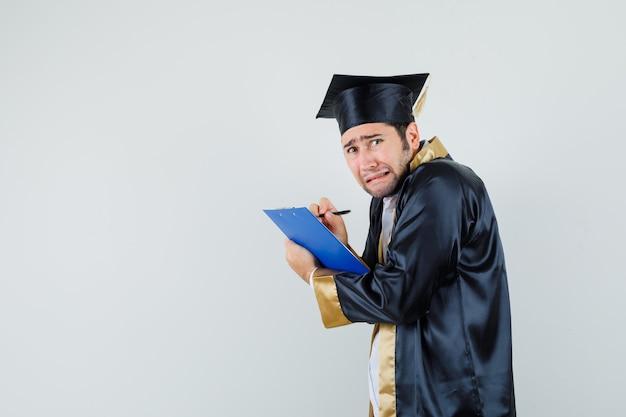 Młody człowiek robienie notatek w schowku w mundurze absolwenta i patrząc przygnębiony.