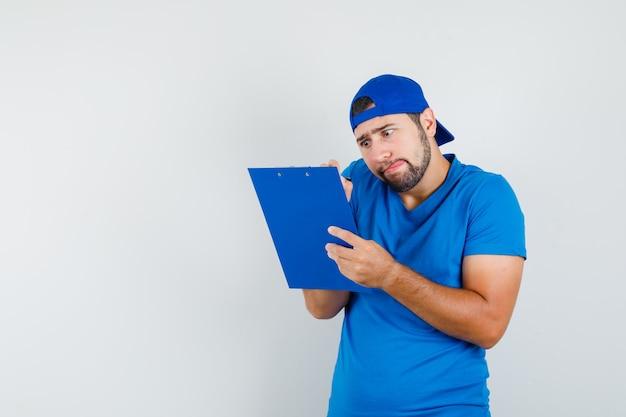 Młody człowiek robienie notatek w schowku w niebieski t-shirt i czapkę i patrząc zwinnie