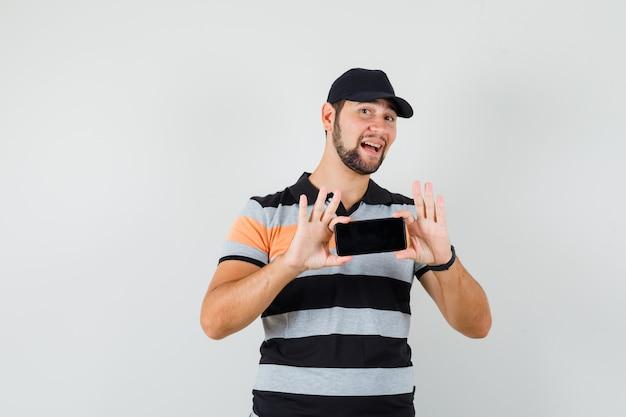 Młody człowiek robienie zdjęć na telefon komórkowy w t-shirt, czapka i wesoły wyglądający.