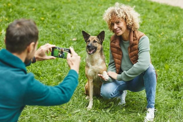 Młody człowiek robienie zdjęć w swoim telefonie komórkowym młodej kobiety i ich zwierzaka na zewnątrz