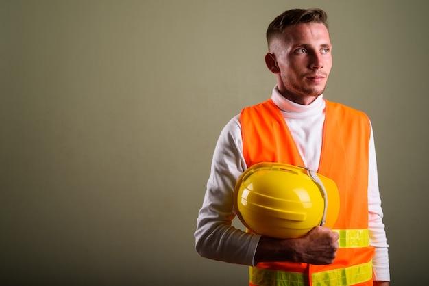 Młody człowiek robotnik budowlany przeciwko kolorowej ścianie