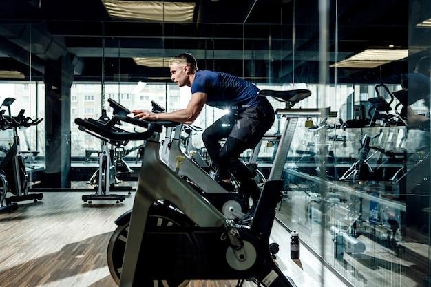 Młody człowiek rower treningowy, jazda na rowerze, ćwiczenia stacjonarne.