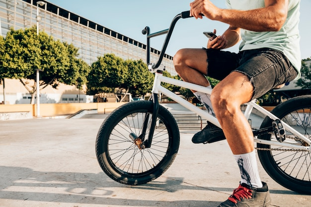 Młody człowiek rowerzysta trzyma jego telefon