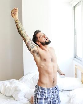 Młody człowiek rozciąga jego ręki na łóżku